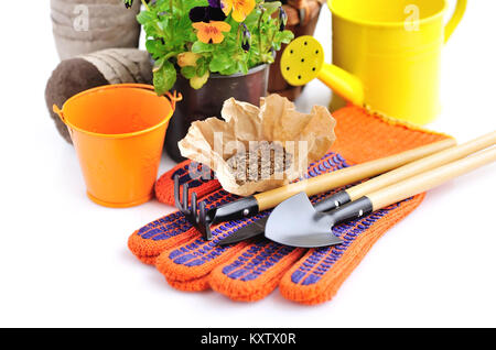 Gardening tools and seed and spring flowers on a white background - Stock Photo