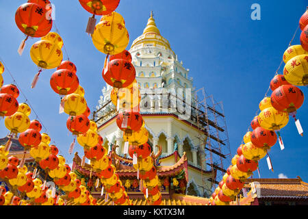 A lot of red and yellow lanterns are hanging as decoration on strings during Chinese New Year. The pagoda of the - Stock Photo