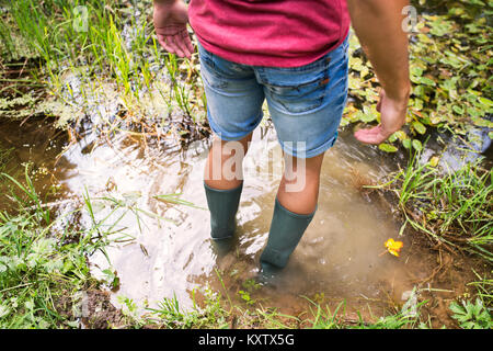 Teenage boy in rubber boots standing in lake. - Stock Photo