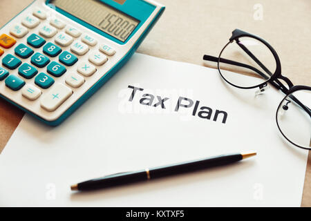Close up tax planning word on paper with calculator, pen and eye glasses place on the wooden table. - Stock Photo