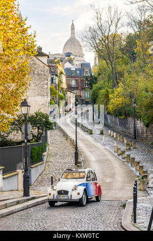 Paris, France - November 19, 2017: Driving the small streets of Montmartre on board a hired vintage french car with - Stock Photo