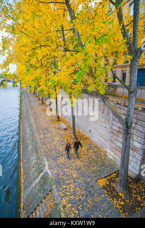 Autumn Paris, a young couple take a walk along an embankment on the Quai de Bourbon in the centre of Paris, France. Stock Photo