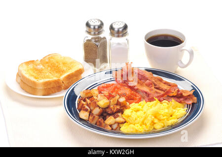 Blue plate breakfast special with scrambled eggs, hash brown potatoes, strips of  bacon, grilled tomatoes, buttered - Stock Photo