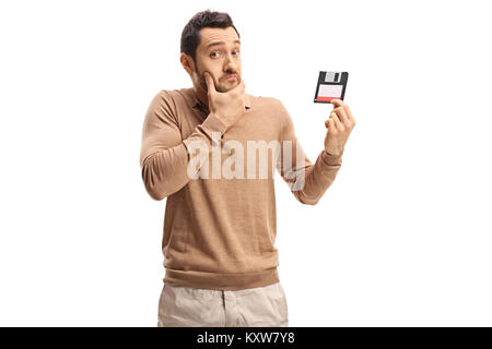 Confused young man holding a floppy disk isolated on white background - Stock Photo