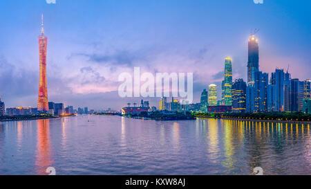 Guangzhou, China skyline on the river at dusk. - Stock Photo