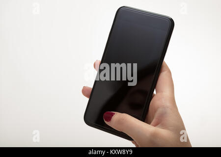 Close-up of the hand of a woman holding a black turned off smartphone against gray background for copy space - Stock Photo