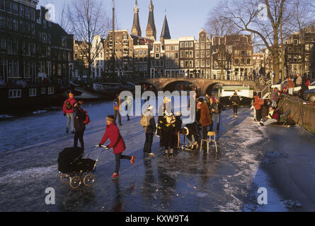 The Netherlands. Amsterdam. Center. Canal called Keizersgracht. Woman skating with buggy on frozen canal. Winter. - Stock Photo