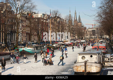The Netherlands, Amsterdam, Winter, ice skating on frozen canals. Keizersgracht. 17th century houses. - Stock Photo
