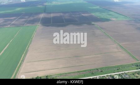Fields in the Kuban view from a height. Young wheat and plowed field a little further from the village. The flight - Stock Photo