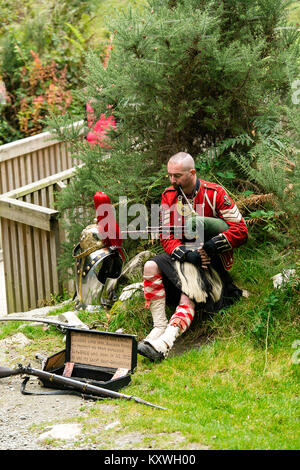 Man busking dressed in Scottish Soldier Outfit sitting by his armor and playing bagpipes at the entrance to the - Stock Photo