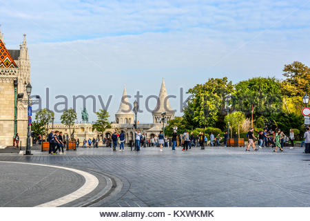 Matthias Square with the Matthias Church and the Fisherman's Bastion with tourists enjoying the sunny day in Budapest - Stock Photo
