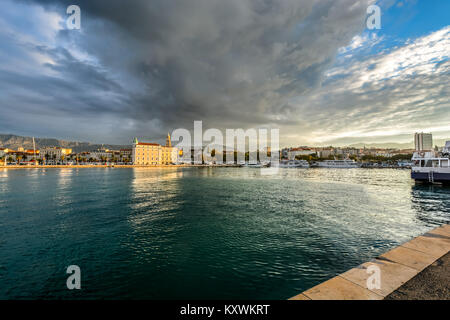 Early morning on the Dalmatian coast of the Adriatic Sea at the Split Harbour Port as storm clouds come in and the - Stock Photo
