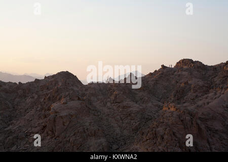two people in the distance standing on top of a mountain range in evening light having a photograph taken. - Stock Photo