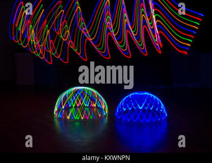 multi-coloured light trails patterns in waves above multi-coloured light dome and blue light dome - abstract painting - Stock Photo