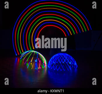 multi-coloured light trails patterns in shape of arc rainbow above multi-coloured and blue light domes - abstract - Stock Photo
