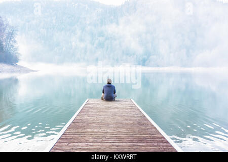 Young man sitting and meditating on the dock of a lake on a foggy day of winter, Vosges, France - Stock Photo