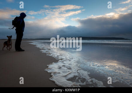 Man walking dog on the Big Strand beach in beautiful evening light in winter, Isle of Islay, Scotland - Stock Photo