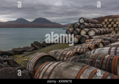 Scottish landscapes with whisky barrels stacked up at the Bunnahabhain Distillery and views of Isle of Jura, Isle - Stock Photo