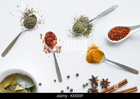 Top view of various dried aromatic spices in metal and ceramic spoons  - Stock Photo