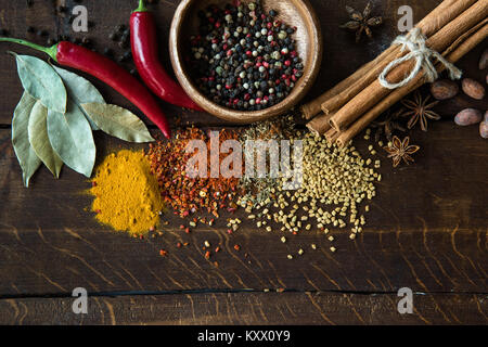 pepper in bowl with scattered herbs and spices, laurel leaves, chili peppers on wooden tabletop - Stock Photo