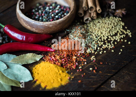 close up of pepper in bowl with scattered spices, laurel leaves, chili peppers on wooden tabletop - Stock Photo