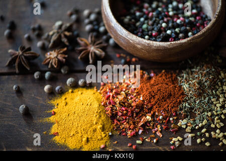different kinds of pepper in bowl and spices with herbs scattered on wooden tabletop - Stock Photo