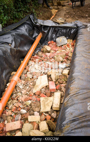 A newly dug pit filled with brick and stone rubble to form a rainwater soakawy from building foundations in UK - Stock Photo