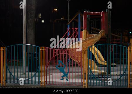 empty illuminated childrens slide in a playground at night - Stock Photo