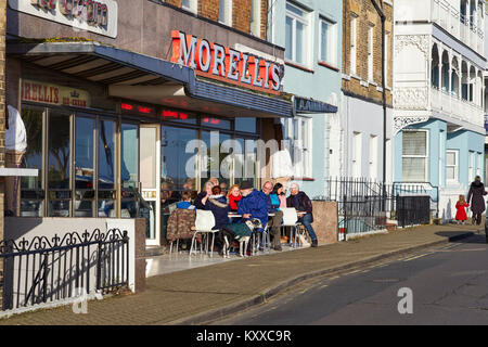 People sitting outside Morellis ice cream parlour in Broadstairs, Kent on winters afternoon - Stock Photo