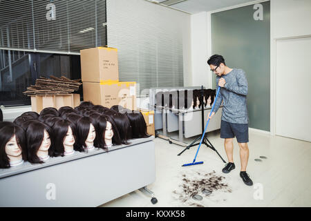 Bearded man wearing glasses standing indoors, sweeping hair on floor, large group of mannequin heads with brown - Stock Photo