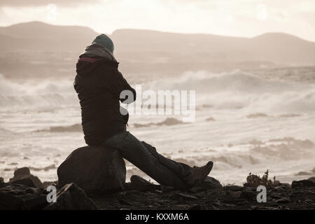 Woman looking out over a stormy sea - Stock Photo