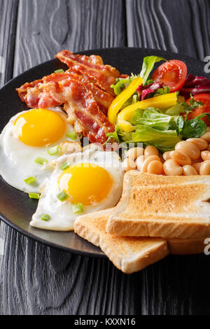 English homemade breakfast: fried eggs with bacon, beans, toast and fresh vegetables on a plate on the table. vertical - Stock Photo