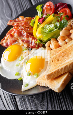 hearty breakfast: fried eggs with bacon, beans, toast and fresh vegetable salad on a plate on the table. vertical - Stock Photo