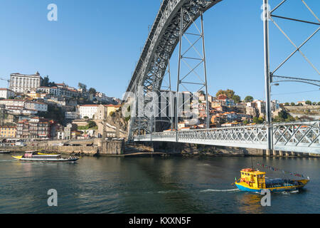 the River Douro waterfront looking towards the Ribeira district of Porto, Portugal. with the Dom Luis I Bridge in - Stock Photo