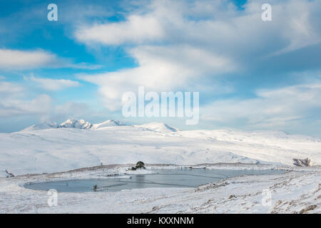 Home Loch in the Scottish Highlands frozen over on a sunny snowy day with mountain view behind, Meall Doire Faid, - Stock Photo