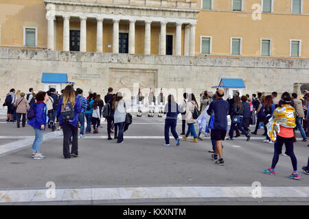 Tourists watching the changing of the Evzones guard ceremony in front of Greek Tomb of Unknown Solder by parliament - Stock Photo