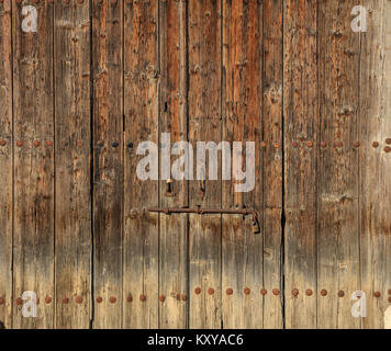 Wooden brown door. Timeworn background with rusty latch and padlock. Close up view with details. - Stock Photo