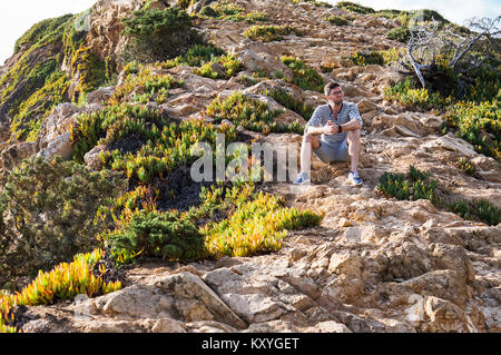 Young and handsome man sitting on a rock after a walk among poor vegetation and stones - Stock Photo