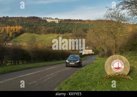 Car passing boundary stone marking entrance to North York Moors National Park & Kilburn white horse carved on hillside - Stock Photo