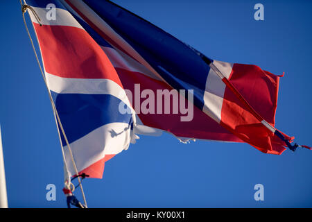 A tattered Union Jack flag fluttering in the wind against a blue sky. - Stock Photo