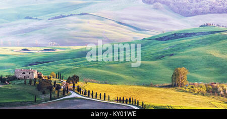TUSCANY, ITALY - APRIL 14, 2014: Typical idyllic sunset on a Tuscan farm. Hilly plowed fields in different colors, - Stock Photo