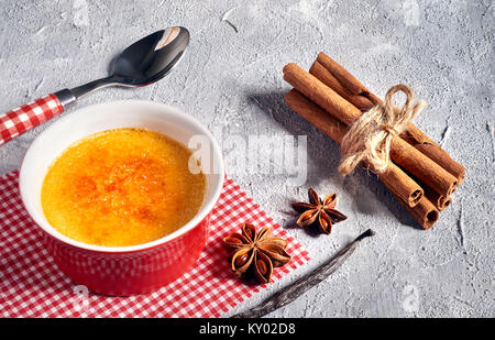Creme brulee (cream brulee, burnt cream) on red-white checkered napkin with matching spoon, cinnamon sticks and - Stock Photo