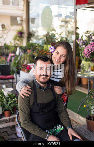 Smiling florist couple in a flower shop. Male wearing black apron sitting in a chair and smiling female with a lisianthus - Stock Photo