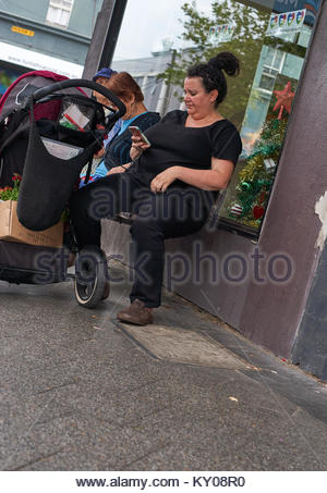 A mother dressed in black, sits on a bench seat on the sidewalk, beside two older women - using her smartphone  - Stock Photo