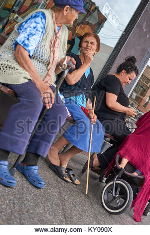 An old woman with a walking-stick, another with a blind-person's cane; and a mum with a baby in a pram - using her - Stock Photo
