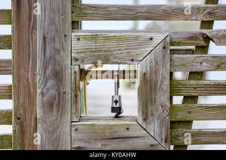 padlock on wooden gate - Stock Photo