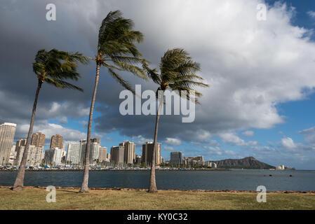 Diamond Head, Waikiki and Honolulu skyline viewed from Magic Island with palm trees in the foreground - Stock Photo