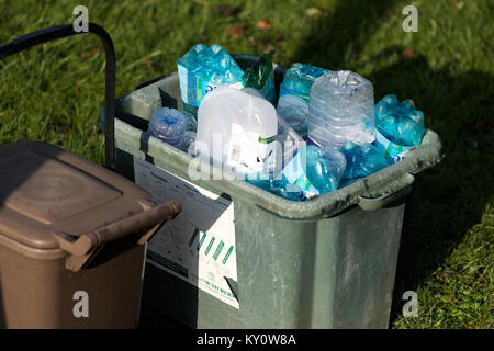 A local authority waste recycle outside a house for collection and recycling. It's full of assorted packaging plastics - Stock Photo