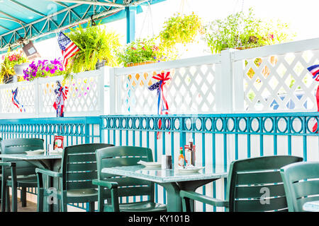 Empty seaside seafood outdoor, outside restaurant tables with summer plants, American flags and nobody - Stock Photo