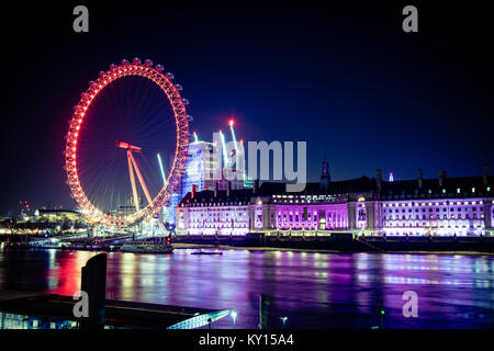 The London eye and the Thames river lit up at night. - Stock Photo